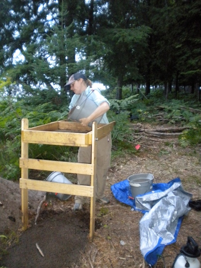 Fierce and productive archaeologist Ashley Schubert screens a bucket, hunting for artifacts in northern Michigan.